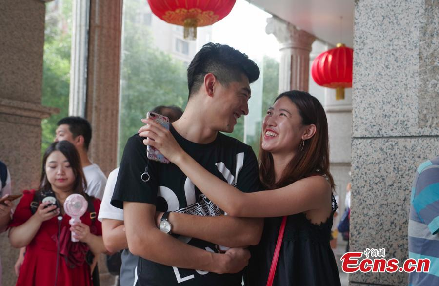 A couple poses for a photo as they complete their marriage registration at the civil affairs department in Taiyuan City, Shanxi Province, Aug. 17, 2018 on the Qixi Festival, known as China's Valentine\'s Day. Falling on the seventh day of the seventh lunar month on the Chinese calendar, the festival celebrates the annual meeting of a cowherd and weaver girl in Chinese mythology. Some reportedly got up at 5 am to register on a day considered auspicious. (Photo: China News Service/Wu Junjie)