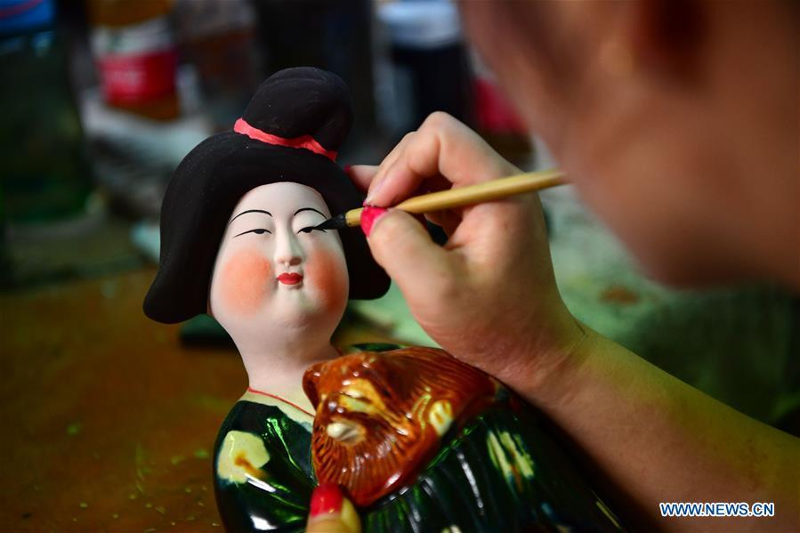 An artisan works at a workshop of Gao Shuiwang, a tri-colored glazed pottery technique inheritor, in Nanshishan Village, Mengjin County, Luoyang City, central China\'s Henan Province, Aug. 15, 2018. Gao is a leading figure in the revival of tri-colored glazed pottery, or Sancai, a Chinese porcelain characterized by a glaze with three intermingled colours. The producing technique of Sancai, which flourished in the Tang Dynasty (618-907 AD), was very complex and listed as one of China\'s National Intangible Heritages in 2008. Nanshishan Village in Henan is regarded as an important village of Sancai culture, with more than 70 enterprises now engaging in the industry. (Xinhua/Feng Dapeng)