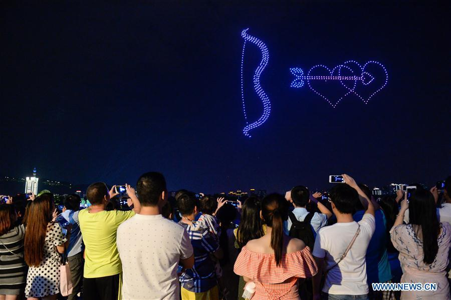 People view drones performance at the Orange Isle scenic area in Changsha, central China\'s Hunan Province, Aug. 16, 2018. Groups of drones performed a light show here to greet the Qixi festival, or Chinese Valentine\'s Day, which falls on Aug. 17 this year. (Xinhua/Zhang Xiaoyu)