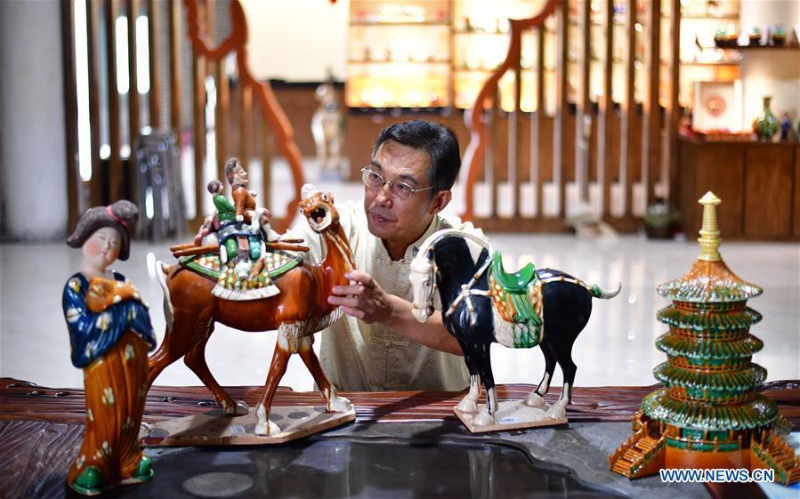 Tri-colored glazed pottery technique inheritor Gao Shuiwang checks horse potteries in Nanshishan Village, Mengjin County, Luoyang City, central China\'s Henan Province, Aug. 15, 2018. Gao is a leading figure in the revival of tri-colored glazed pottery, or Sancai, a Chinese porcelain characterized by a glaze with three intermingled colours. The producing technique of Sancai, which flourished in the Tang Dynasty (618-907 AD), was very complex and listed as one of China\'s National Intangible Heritages in 2008. Nanshishan Village in Henan is regarded as an important village of Sancai culture, with more than 70 enterprises now engaging in the industry. (Xinhua/Feng Dapeng)