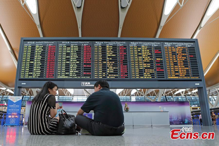 Passengers wait at the departure hall of Pudong International Airport in Shanghai, Aug. 17, 2018. Some flights in Hongqiao International Airport and Putong International Airport in Shanghai were delayed or cancelled due to the Typhoon Rumbia. (Photo: China News Service/Yin Liqin)