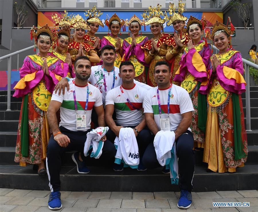 Iranian athletes pose for pictures with etiquette team members in Indonesian folk costume at the Asian Games Village ahead of the 18th Asian Games in Jakarta, Indonesia, on Aug. 16, 2018. (Xinhua/Wang Yuguo)
