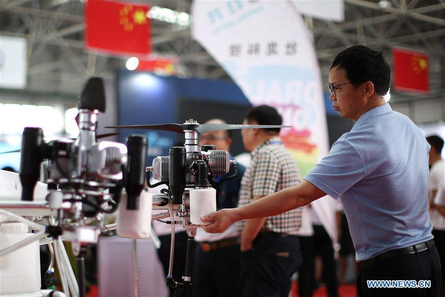 A visitor views a drone displayed during the 7th Faku Flight Conference in Shenyang, capital of northeast China\'s Liaoning Province, Aug. 18, 2018. The flight conference kicked off here on Saturday. (Xinhua/Yao Jianfeng)