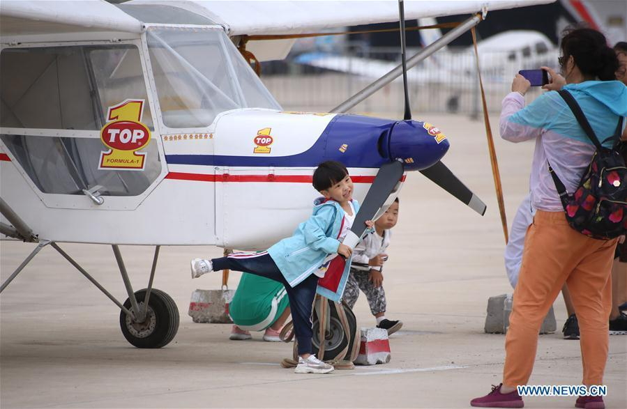 A child poses for photo with a displayed aircraft during the 7th Faku Flight Conference in Shenyang, capital of northeast China\'s Liaoning Province, Aug. 18, 2018. The flight conference kicked off here on Saturday. (Xinhua/Yao Jianfeng)