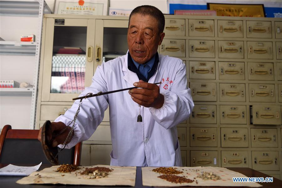 Doctor Wang Guilin dispenses herbs according to a traditional Chinese medicine prescription in Yueming Village of Mawu County in Pingliang, northwest China\'s Gansu Province, Aug. 15, 2018. Wang has been working here as a village-based doctor since 1968. A large number of medical practitioners are active in China\'s rural areas where health care is still underdeveloped. Under adverse working conditions, they have carried forward the humanitarian spirit and devoted themselves to the health of rural citizens. China will mark its first Medical Workers\' Day on Aug. 19, 2018. (Xinhua/Fan Peishen)