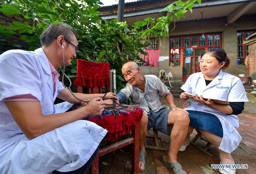 Doctors Zhai Dalong (L) and Wang Cuihong (R) measure blood pressure for a patient in Xudi Village of Daming County in Handan, north China\'s Hebei Province, Aug. 16, 2018. Zhai and Wang are husband and wife. A large number of medical practitioners are active in China\'s rural areas where health care is still underdeveloped. Under adverse working conditions, they have carried forward the humanitarian spirit and devoted themselves to the health of rural citizens. China will mark its first Medical Worker\'s Day on Aug. 19, 2018. (Xinhua/Wang Xiao)