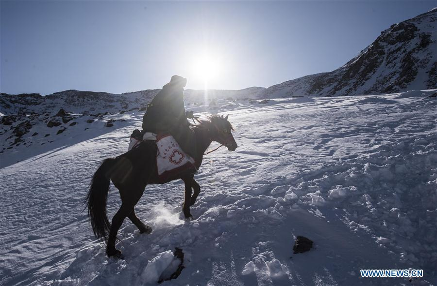 Doctor Yelixat and his horse pass through snow-covered slope during a medical service trip around a pastoral area in Tekes County of Ili Kazakh Autonomous Prefecture, northwest China\'s Xinjiang Uygur Autonomous Region, Dec. 15, 2017. A large number of medical practitioners are active in China\'s rural areas where health care is still underdeveloped. Under adverse working conditions, they have carried forward the humanitarian spirit and devoted themselves to the health of rural citizens. China will mark its first Medical Workers\' Day on Aug. 19, 2018. (Xinhua/Jiang Wenyao)