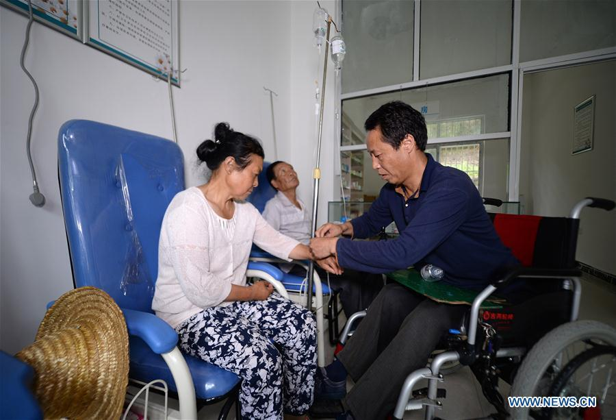 Doctor Sun Qingyong (R) gives a patient intravenous injection at a clinic in Shaluo Village of Guanghuojie Township in Ningshan County, Ankang, northwest China\'s Shaanxi Province, Aug. 15, 2018. Sun became paraplegic in a traffic accident 22 years ago. He soon started offering medical treatment to his fellow villagers on a wheelchair. A large number of medical practitioners are active in China\'s rural areas where health care is still underdeveloped. Under adverse working conditions, they have carried forward the humanitarian spirit and devoted themselves to the health of rural citizens. China will mark its first Medical Workers\' Day on Aug. 19, 2018. (Xinhua/Liu Xiao)