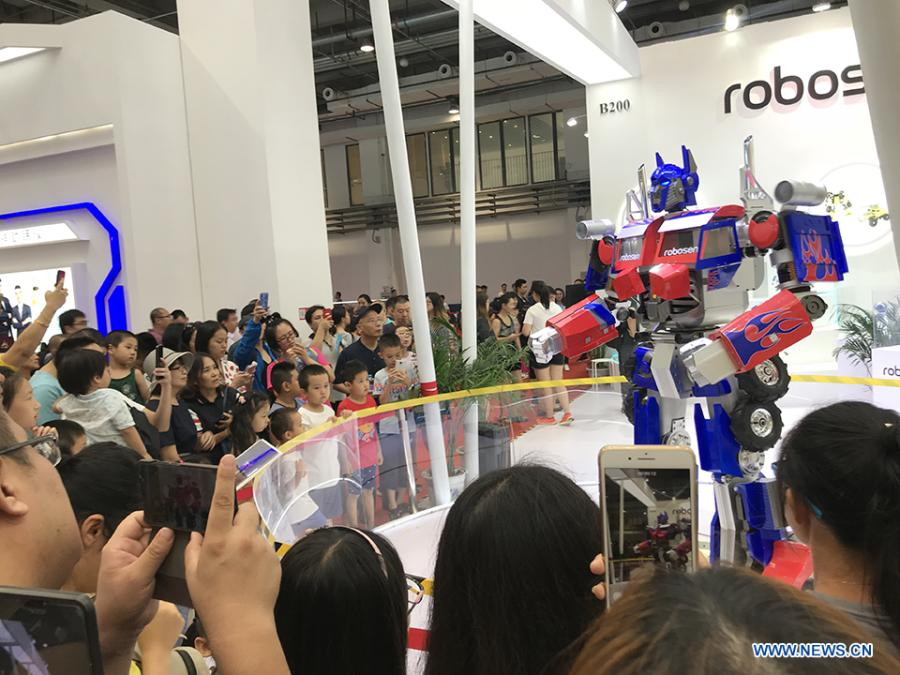Visitors watch a robot performing at the 2018 World Robot Conference in Beijing, Aug. 17, 2018. The conference attracts a total of 166 domestic and international enterprises exhibiting their cutting edge technologies and more than 500 items are displayed at the scene. (Xinhuanet/Liang Yurou)
