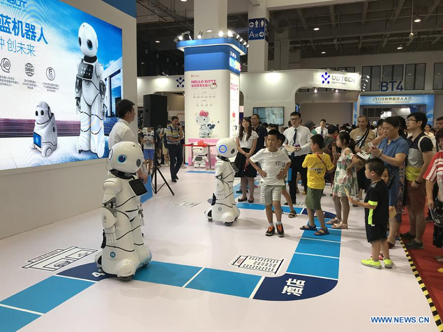 Visitors watch robots performing at the 2018 World Robot Conference in Beijing, Aug. 17, 2018. The conference attracts a total of 166 domestic and international enterprises exhibiting their cutting edge technologies and more than 500 items are displayed at the scene. (Xinhuanet/Liang Yurou)