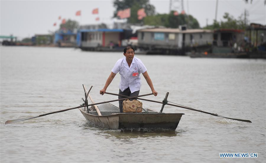 Doctor Li Shaoyou rows a boat on his way to a patient\'s home in Mudundao Village of Bancheng Township, Sihong County, east China\'s Jiangsu Province, June 27, 2018. Li has been offering medical services to fishermen around the Hongze Lake for more than three decades. A large number of medical practitioners are active in China\'s rural areas where health care is still underdeveloped. Under adverse working conditions, they have carried forward the humanitarian spirit and devoted themselves to the health of rural citizens. China will mark its first Medical Workers\' Day on Aug. 19, 2018. (Xinhua/Ji Chunpeng)