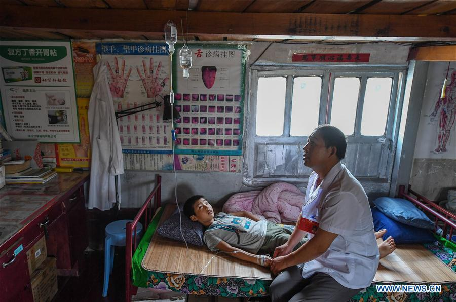 Doctor Li Shaoyou treats a young patient at his boat clinic in Mudundao Village of Bancheng Township, Sihong County, east China\'s Jiangsu Province, June 27, 2018. Li has been offering medical services to fishermen around the Hongze Lake for more than three decades. A large number of medical practitioners are active in China\'s rural areas where health care is still underdeveloped. Under adverse working conditions, they have carried forward the humanitarian spirit and devoted themselves to the health of rural citizens. China will mark its first Medical Workers\' Day on Aug. 19, 2018. (Xinhua/Ji Chunpeng)