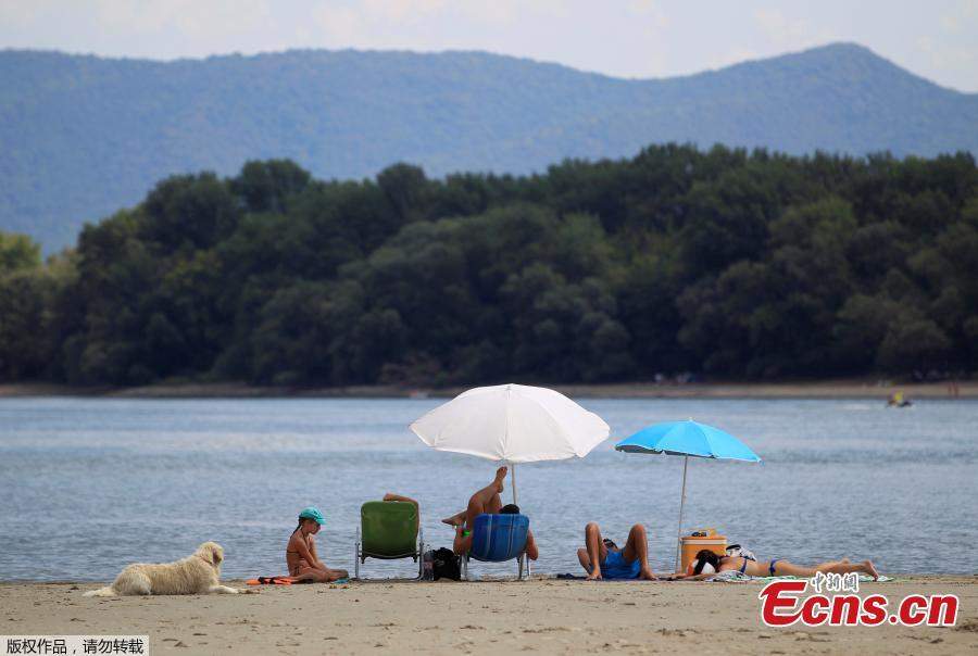 People enjoy warm weather on a gravel shoal in the middle of the Danube river during the period of low water level near Esztergom, Hungary, August 19, 2018. (Photo/Agencies)