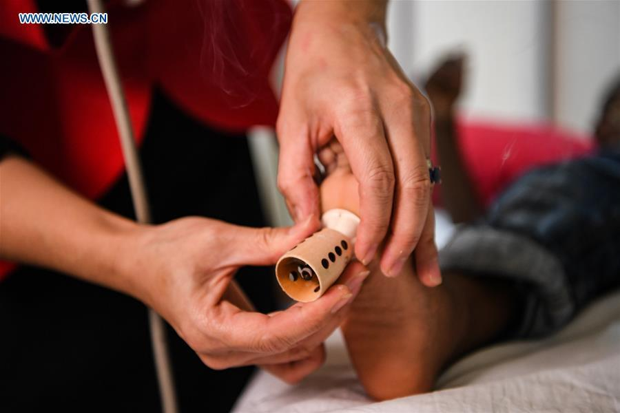 Pan Lianxue does moxibustion treatment for a local patient at her clinic in Nairobi, Kenya, Aug. 17, 2018. Pan Lianxue and her husband Luo Zhanliang, both Chinese doctors in traditional Chinese medicine, have been operated a clinic in Nairobi for over 20 years attracting more and more African patients. China issued the first Medical Workers\' Day on Aug. 19.(Xinhua/Li Yan)