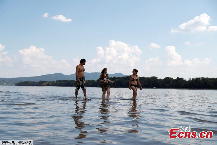 People walk in the middle of the Danube river during the period of low water level near Esztergom, Hungary, August 19, 2018. (Photo/Agencies)