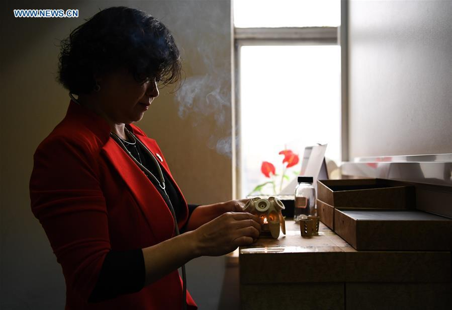 Pan Lianxue prepares to practise moxibustion treatment for a local patient at her clinic in Nairobi, Kenya, Aug. 17, 2018. Pan Lianxue and her husband Luo Zhanliang, both Chinese doctors in traditional Chinese medicine, have been operated a clinic in Nairobi for over 20 years attracting more and more African patients. China issued the first Medical Workers\' Day on Aug. 19.(Xinhua/Li Yan)