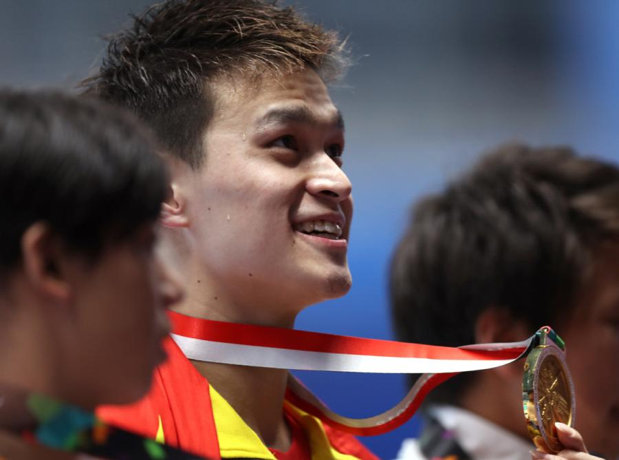China\'s Sun Yang shows his gold medal after winning the gold medal at men\'s 200m freestyle final at the GBK Aquatics Center in Jakarta, Indonesia on Aug. 19, 2018. (Photo/Xinhua)