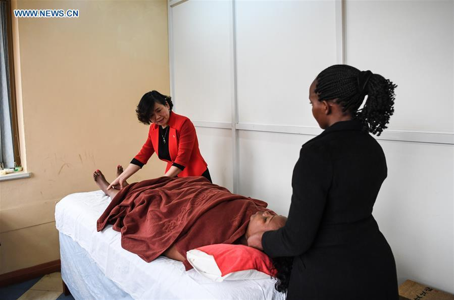 Pan Lianxue shows the skills of tui na (Chinese therapeutic massage) to her local employee at her clinic in Nairobi, Kenya, Aug. 17, 2018. Pan Lianxue and her husband Luo Zhanliang, both Chinese doctors in traditional Chinese medicine, have been operated a clinic in Nairobi for over 20 years attracting more and more African patients. China issued the first Medical Workers\' Day on Aug. 19.(Xinhua/Li Yan)