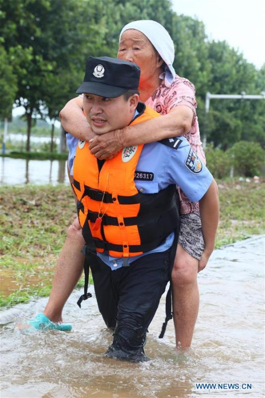A rescuer transfers an old woman in flood in Huaibei City, east China\'s Anhui Province, Aug. 19, 2018. Typhoon Rumbia has brought heavy rain to Huaibei and some places in Huaibei were inundated by flood. (Xinhua/Wan Shanchao)