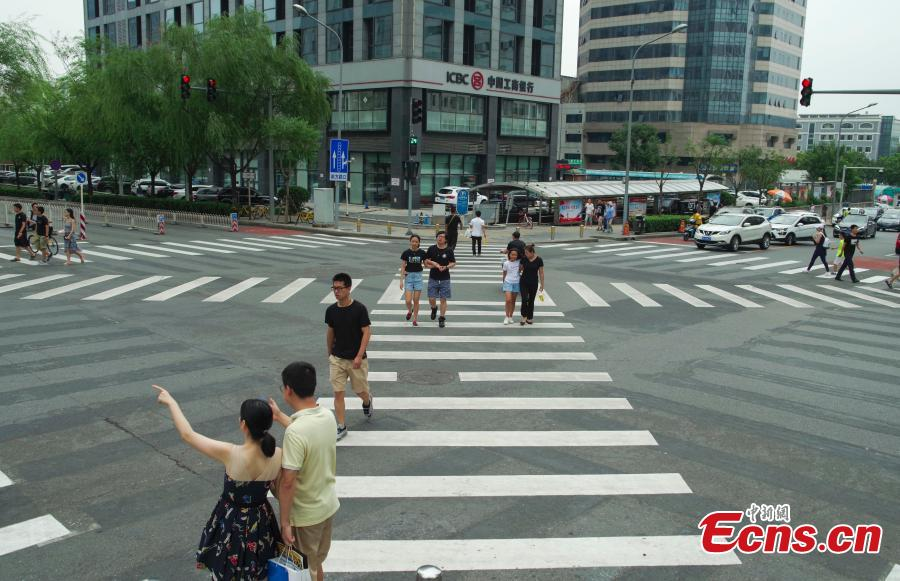 A new pedestrian crossing layout at the intersection of Lugu West Road and Zhengda Road in Shijiangshan District, Beijing, Aug. 19, 2018. When given the green light, pedestrians can choose to cross the intersection diagonally to get to the opposite corner in addition to simply crossing from one side of the road to the other. It is believed to be the first intersection with such an option for pedestrians in Beijing. (Photo: China News Service/Jia Tianyong)