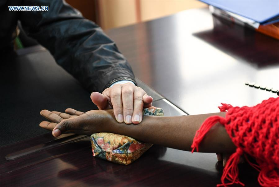 Luo Zhanliang feels the pulse on a patient\'s wrist at his clinic in Nairobi, Kenya, Aug. 17, 2018. Luo Zhanliang and his wife Pan Lianxue, both Chinese doctors in traditional Chinese medicine, have been operated a clinic in Nairobi for over 20 years attracting more and more African patients. China issued the first Medical Workers\' Day on Aug. 19. (Xinhua/Li Yan)