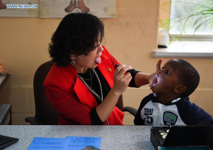Pan Lianxue examines a local child at her clinic in Nairobi, Kenya, Aug. 17, 2018. Pan Lianxue and her husband Luo Zhanliang, both Chinese doctors in traditional Chinese medicine, have been operated a clinic in Nairobi for over 20 years attracting more and more African patients. China issued the first Medical Workers\' Day on Aug. 19.(Xinhua/Li Yan)