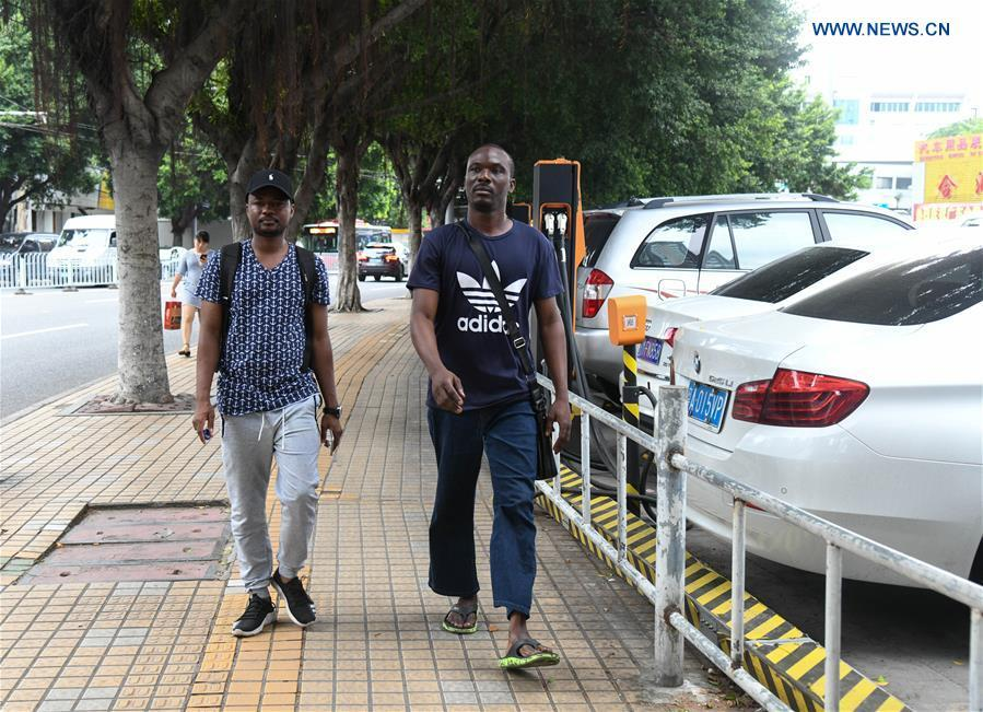 Mansur Barhama Abulfathi (L) from Nigeria walks on a road with his friend in Guangzhou, south China\'s Guangdong Province, Aug. 14, 2018. This 24-year-old young man has a Chinese name Quan Xiaobao. Quan Xiaobao has lived in Guangzhou for over one year, and his fluency in Chinese allows him to work part-time as a translator and business consultant. Located near Hong Kong and Macao special administrative regions, Guangzhou attracts many Africans to work or study here. Guangzhou government has stepped up the work to provide all-round service for foreigners to help them adapt to the local environment. (Xinhua/Deng Hua)