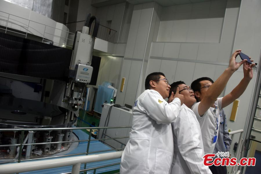 Researchers with the CAS Changchun Institute of Optics, Fine Mechanics and Physics pose for a photo after a silicon carbide (SiC) single mirror blank with a diameter of 4.03 m was given the OK for project use in Changchun City, Northeast China's Jilin Province, Aug. 21, 2018. The mirror blank is a vital component for creating a large-scale telescope, and the bigger it is the more capable it is of detecting visible light bands. (Photo: China News Service/Sun Zifa)