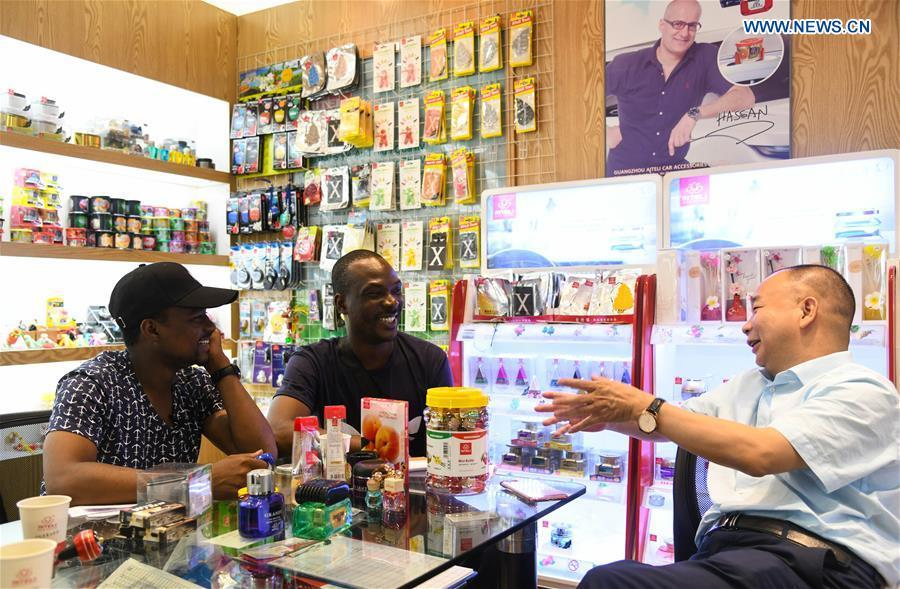 Mansur Barhama Abulfathi (L) from Nigeria translates for his friend at a company in Guangzhou, south China\'s Guangdong Province, Aug. 14, 2018. This 24-year-old young man has a Chinese name Quan Xiaobao. Quan Xiaobao has lived in Guangzhou for over one year, and his fluency in Chinese allows him to work part-time as a translator and business consultant. Located near Hong Kong and Macao special administrative regions, Guangzhou attracts many Africans to work or study here. Guangzhou government has stepped up the work to provide all-round service for foreigners to help them adapt to the local environment. (Xinhua/Deng Hua)