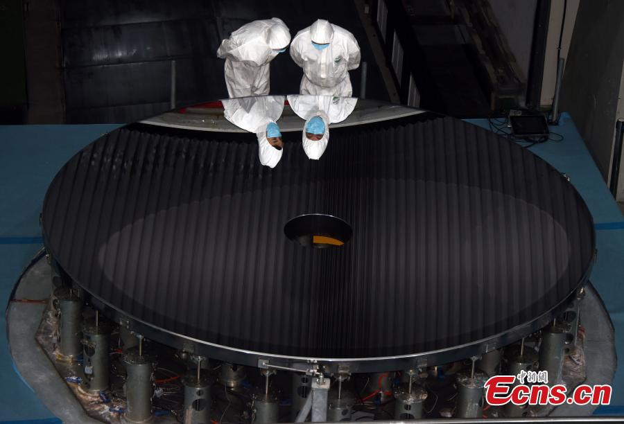 Researchers with the CAS Changchun Institute of Optics, Fine Mechanics and Physics show a silicon carbide (SiC) single mirror blank with a record-breaking diameter of 4.03m, which has passed the testing process for project acceptance, in Changchun City, Northeast China's Jilin Province, Aug. 21, 2018. The mirror blank is a vital component for creating a large-scale telescope, and the bigger it is the more capable it is of detecting visible light bands. (Photo: China News Service/Sun Zifa)