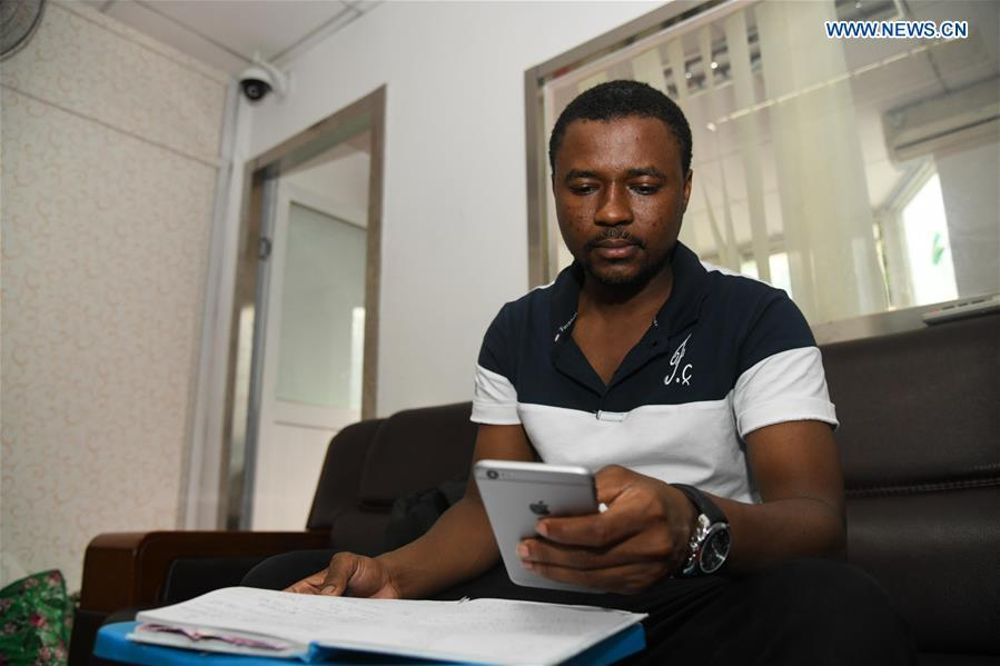Mansur Barhama Abulfathi from Nigeria checks up accounts at an office room in Guangzhou, south China\'s Guangdong Province, Aug. 15, 2018. This 24-year-old young man has a Chinese name Quan Xiaobao. Quan Xiaobao has lived in Guangzhou for over one year, and his fluency in Chinese allows him to work part-time as a translator and business consultant. Located near Hong Kong and Macao special administrative regions, Guangzhou attracts many Africans to work or study here. Guangzhou government has stepped up the work to provide all-round service for foreigners to help them adapt to the local environment. (Xinhua/Deng Hua)