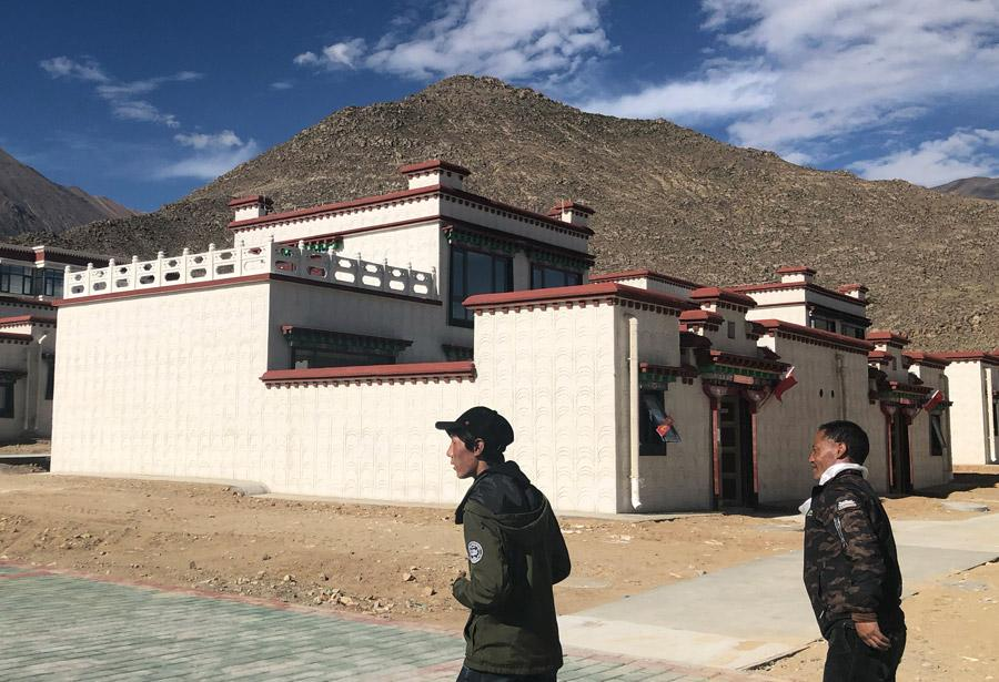 Siyo Tsenga and his son Tagyal head to their new house in a settlement in Doilungdechen district in Lhasa, Tibet autonomous region. [Photo by PALDEN NYIMA/CHINA DAILY]