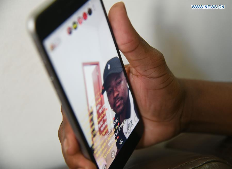 Mansur Barhama Abulfathi from Nigeria communicates with fans on-line at his apartment in Guangzhou, south China\'s Guangdong Province, Aug. 13, 2018. This 24-year-old young man has a Chinese name Quan Xiaobao. Quan Xiaobao has lived in Guangzhou for over one year, and his fluency in Chinese allows him to work part-time as a translator and business consultant. Located near Hong Kong and Macao special administrative regions, Guangzhou attracts many Africans to work or study here. Guangzhou government has stepped up the work to provide all-round service for foreigners to help them adapt to the local environment. (Xinhua/Deng Hua)