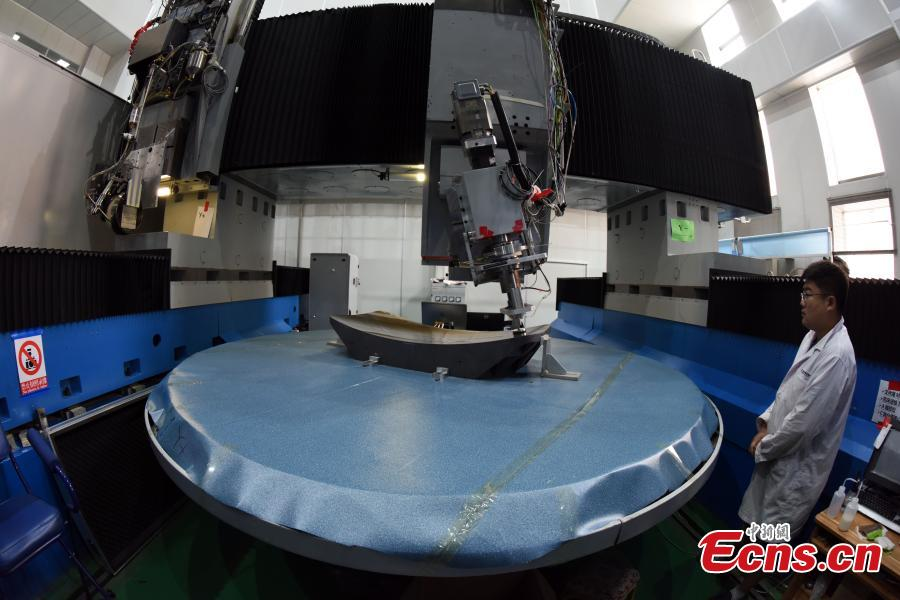 A researcher with the CAS Changchun Institute of Optics, Fine Mechanics and Physics shows the production process of a silicon carbide (SiC) single mirror blank with a diameter of 3m in Changchun City, Northeast China's Jilin Province, Aug. 21, 2018. The mirror blank is a vital component for creating a large-scale telescope, and the bigger it is the more capable it is of detecting visible light bands. (Photo: China News Service/Sun Zifa)
