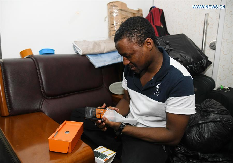 Mansur Barhama Abulfathi from Nigeria checks a Chinese-made smartphone to be brought back to his hometown in Guangzhou, south China\'s Guangdong Province, Aug. 15, 2018. This 24-year-old young man has a Chinese name Quan Xiaobao. Quan Xiaobao has lived in Guangzhou for over one year, and his fluency in Chinese allows him to work part-time as a translator and business consultant. Located near Hong Kong and Macao special administrative regions, Guangzhou attracts many Africans to work or study here. Guangzhou government has stepped up the work to provide all-round service for foreigners to help them adapt to the local environment. (Xinhua/Deng Hua)