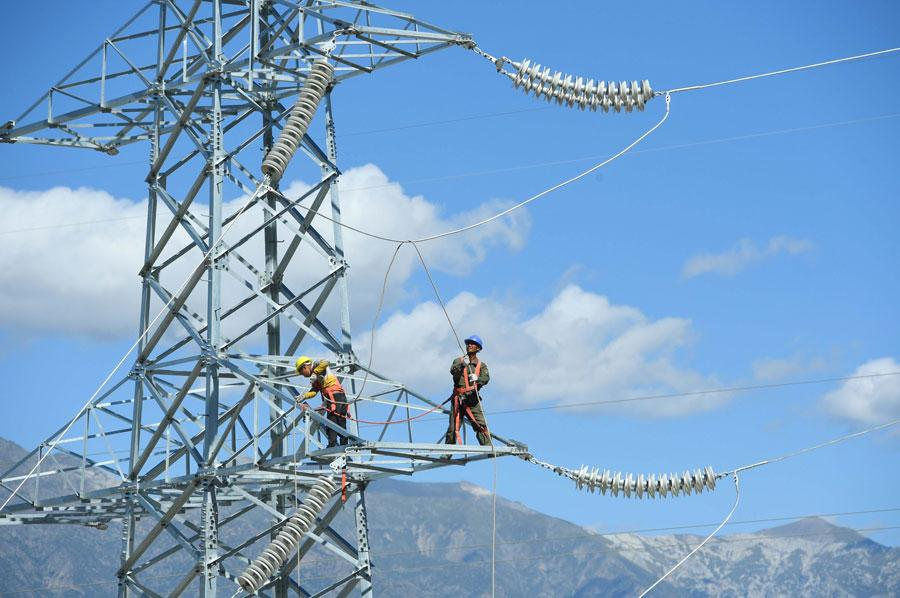 An employee connects electrical cables atop a 30-meter-high, 110 kV power transmission tower in the Tibet autonomous region. (Photo by Song Weixing/For China Daily)
