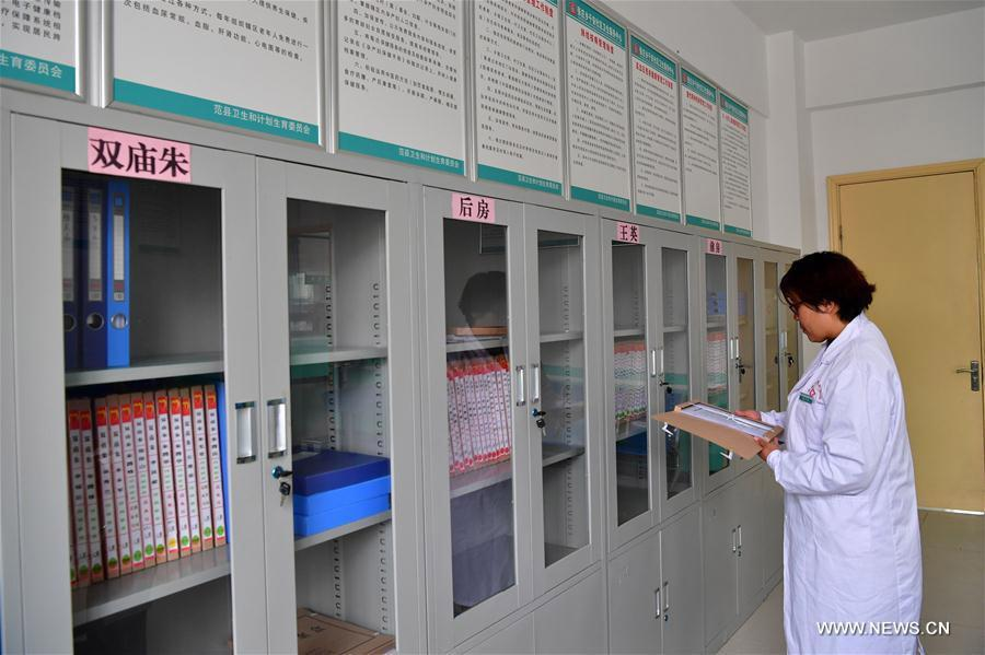 A doctor checks residents\' health files at a resettlement community at Zhangzhuang township of Fanxian county, Central China\'s Henan Province, Nov. 1, 2017. (Photo/Xinhua)