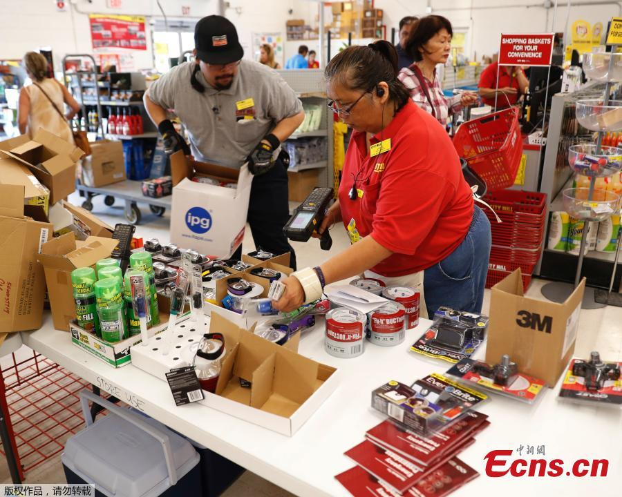 City Mill hardware store sales associates Frank Miller Gascon, left, Lisa Lavilla, fill a table up with duck tape, flashlights, and other hurricane supplies in Honolulu, Aug. 22, 2018. Gascon said he\'s been filling the table up every ten minutes as supplies are being swept up by shoppers who are preparing for the approaching Hurricane Lane. (Photo/Agencies)