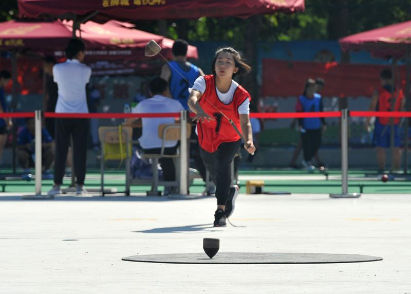 A player is spinning a peg-top at the 10th Provincial Traditional Ethnic Sports Games in Hebei Province, Aug. 21, 2018.  (Photo by Yuan Liwei for chinadaily.com.cn)