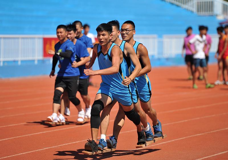 Competitors are race walking with team members' feet fastened to a board at the 10th Provincial Traditional Ethnic Sports Games in Hebei Province, Aug. 21, 2018.  (Photo by Yuan Liwei for chinadaily.com.cn)