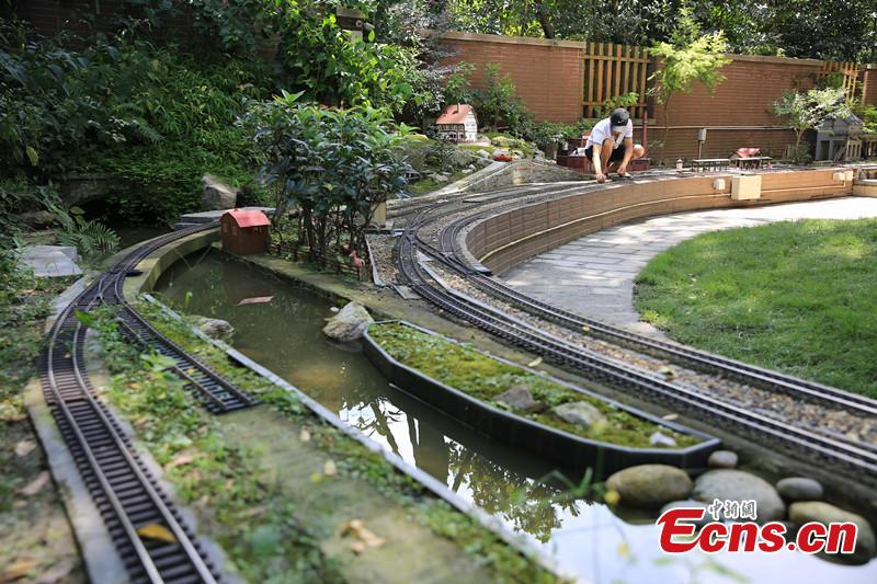 Zhang Yong'an, 63, and his family members have spent five years and more than one million yuan ($145,000) building a 'train kingdom\' in their 330-sqm home garden in Wenjiang District, Chengdu City, Southwest China's Sichuan Province. A great fan of train models from an early age, Zhang has tried his best to present every part of a real railway station with vivid models, including train lights, tunnels, passengers, platforms, freight trains and passenger trains. When it rains, Zhang drives all the trains indoors by remote control. (Photo: China News Service/Wu Pinghua)