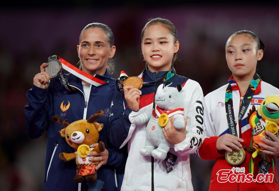 (L to R) Silver medalist Oksana Chusovitina of Uzbekistan, gold medalist Yeo Seojeong of South Korea and bronze medalist Pyon Rye Yong of the DPRK celebrate on the podium the Artistic Gymnastics Women\'s Vault in Jakarta, Indonesia on Aug.23, 2018. (Photo: China News Service/Hou Yu)