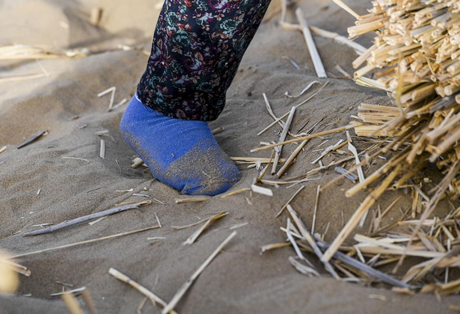 Because of the difficulty of walking in the desert, some of the women work only in socks. (Photo/Xinhua)