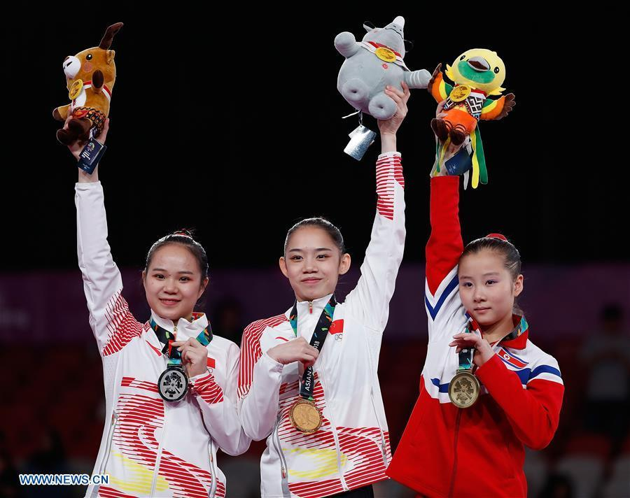 Gold medalist Liu Tingting (C) of China shows medal with silver medalist Luo Huan of China (L) and bronze medalist Jon Jang Mi of the DPRK during the awarding ceremony for the Artistic Gymnastics Women\'s Uneven Bars Final at the Asian Games 2018 in Jakarta, Indonesia on Aug. 23, 2018. (Xinhua/Wang Lili)