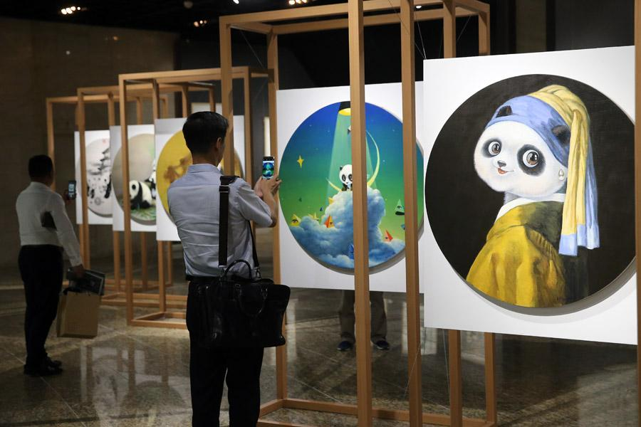 Visitors take photos at the China Giant Panda International Culture Week in Beijing on Thursday. (Photo/CHINA DAILY)  \