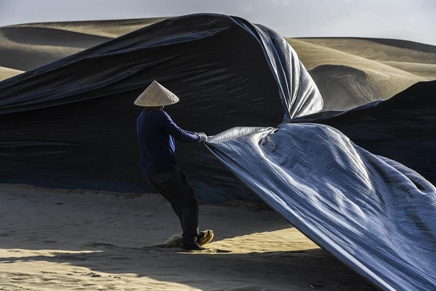 A worker covers the roadbed with woven plastic film before the arrival of a sandstorm. (Photo/Xinhua)