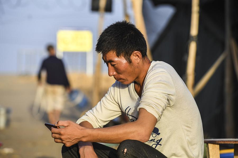 Xie Chunlong, a worker from Qinghai province, watches a TV drama on his mobile phone on a break from his work building a new road through the Taklimakan Desert in the Xinjiang Uygur autonomous region.  (Photo/Xinhua)
