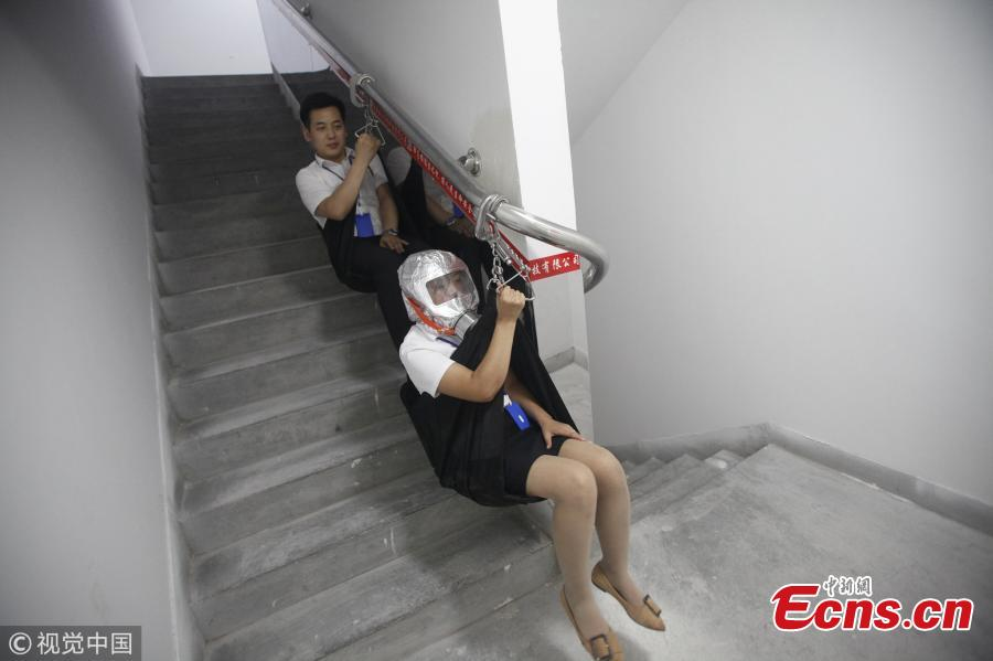 An emergency escape system designed for use in high-rise buildings was unveiled in Xi\'an, Shaanxi Province on Wednesday. If a fire breaks out, people can glide down through the stairwell at a speed of around 1 meter per second using a special railing that can bear the weight of a 100 kilogram person. The emergency exit also has respirators to protect evacuees from poisonous dust and gases. In this photo taken on Wednesday, August 22, 2018 two staff members from the developer of the system demonstrate how it is used. (Photo/VCG)
