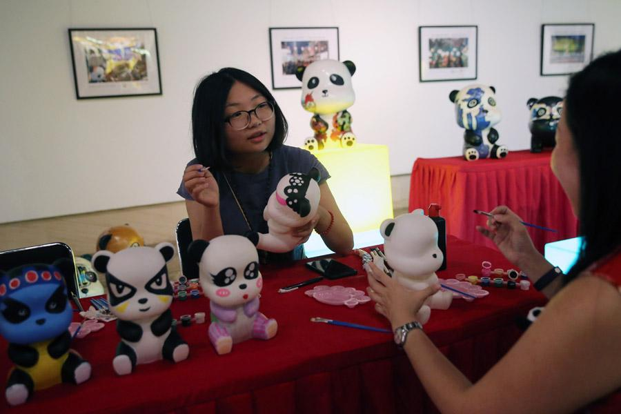 Artists work on panda products at the China Giant Panda International Culture Week in Beijing on Thursday. (Photo/CHINA DAILY)  So far, 58 giant pandas have been involved in international cooperative research projects, and 47 giant panda cubs have been bred abroad, of which 31 have returned to China as required, said Yang Chao, director of the administration\'s wildlife protection department.
