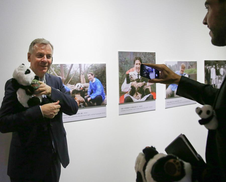 Visitors take photos at the China Giant Panda International Culture Week in Beijing on Thursday. (Photo/CHINA DAILY)  A China Giant Panda Global Promotional Agreement was signed by the center and the China Conservation and Research Center for the Giant Panda, and an exhibition about pandas from Sichuan began on Thursday and will last until next Sunday.  \